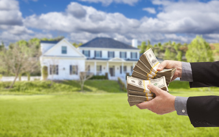 home sale: Man Handing Over Thousands of Dollars in Front of Beautiful House. Stock Photo