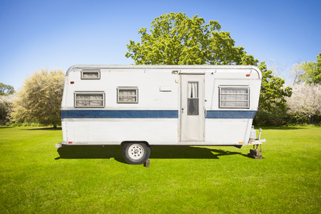 camper trailer: Classic Old Camper Trailer In Grass Field with Beautiful Trees.