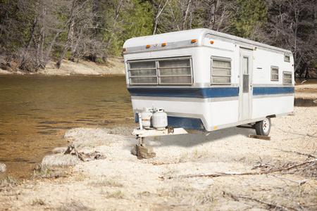 camping pitch: Classic Old Camper Trailer Near A Calm River.