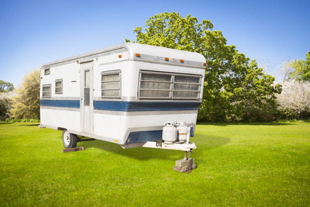 Classic Old Camper Trailer In Grass Field with Beautiful Trees.