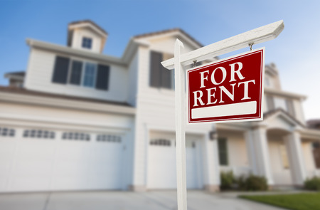 Red For Rent Real Estate Sign in Front of Beautiful House. Stock Photo