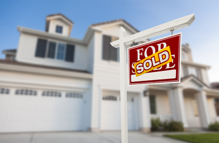 home sale: Sold Home For Sale Real Estate Sign in Front of Beautiful New House. Stock Photo