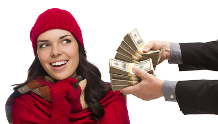 thousands: Mixed Race Young Woman Wearing Holiday Clothes Being Handed Thousands of Dollars Isolated on White. Stock Photo
