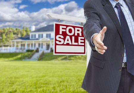 bienes raices: Agente Inmobiliario alcanza para apretón de manos con el signo de la venta y la nueva casa detrás.