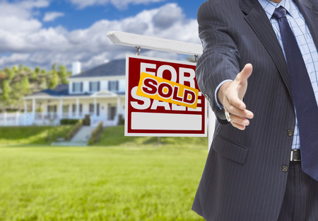 house sale: Real Estate Agent Reaches for Handshake with Sold Sign and New House Behind.