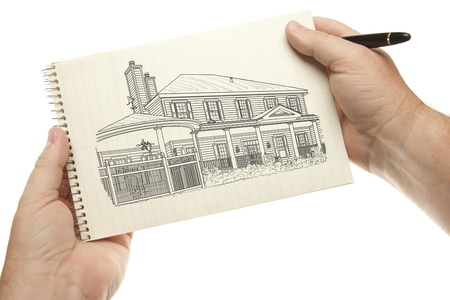 drawing pad: Male Hands Holding Pen and Pad of Paper with House Drawing Isolated on a White Background.