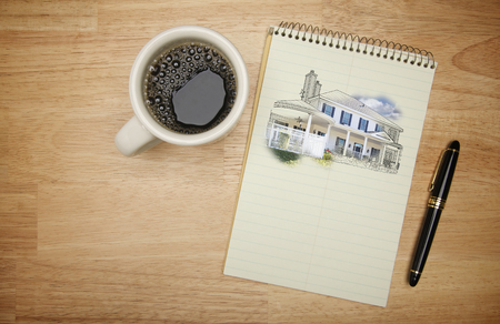 architect drawing: Pad of Paper with House Drawing, Pen and Coffee on Wood Background. Stock Photo