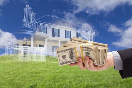 Man Overhandigen duizenden dollars met gedimde House Drawing, Gedeeltelijk Foto en Rolling Green Hills Behind. Stockfoto