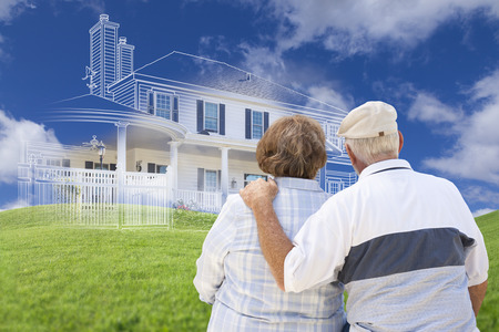 Senior Couple Faces Ghosted House Drawing, Partial Photo and Rolling Green Hills Behind. 스톡 콘텐츠
