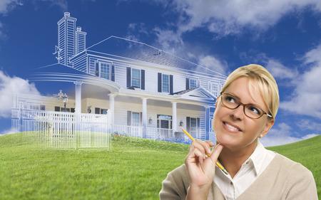 Glimlachende vrouw met potlood op zoek naar gedimde huistekening, gedeeltelijke foto en glooiende groene heuvels erachter.