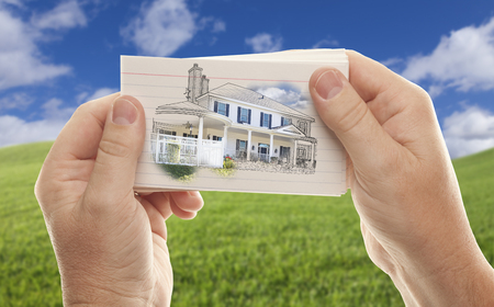 jot: Male Hands Holding Stack of Paper With House Drawing Over Empty Grass Field and Sky.