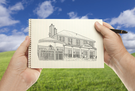 architect drawing: Male Hands Holding Pen and Pad of Paper With House Drawing Over Empty Grass Field and Sky.