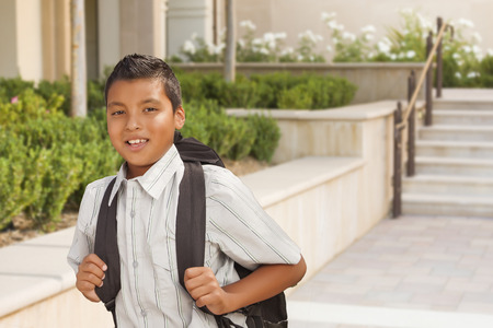 Happy Hispanic Boy with Backpack Walking on School Campus.