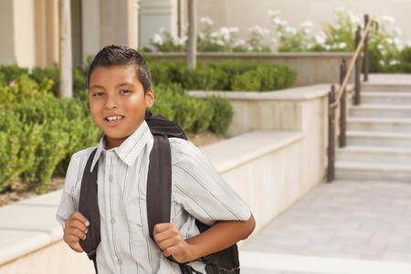 niño con mochila: Muchacho hispánico feliz con Mochila Walking on Campus School.