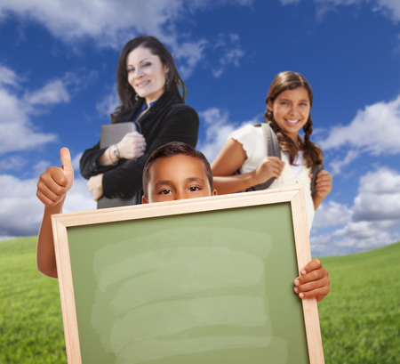 hispanic students: Young Hispanic Students with Blank Chalk Board and Teacher Behind on Grass Field. Stock Photo