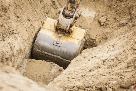 Working Excavator Tractor Digging A Trench. 스톡 콘텐츠