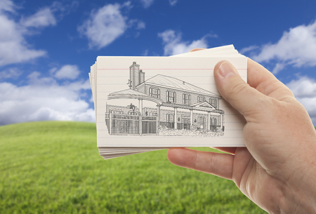architect drawing: Male Hand Holding Stack of Paper With House Drawing Over Empty Grass Field and Sky.