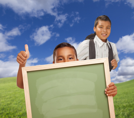 hispanic students: Hispanic Students with Thumbs Up in Grass Field Holding Blank Chalk Board.