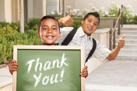 niños latinos: Niños hispanos feliz dando pulgares para arriba Holding Gracias al tablero de tiza Fuera del Campus Escolar.