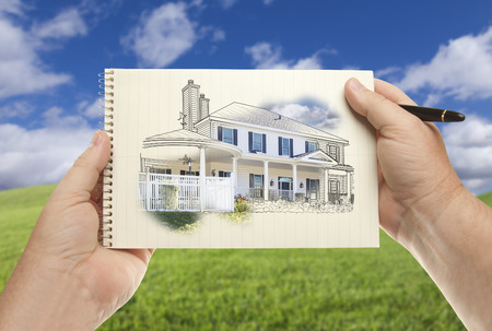 drawing pad: Male Hands Holding Pen and Pad of Paper With House Drawing Over Empty Grass Field and Sky.