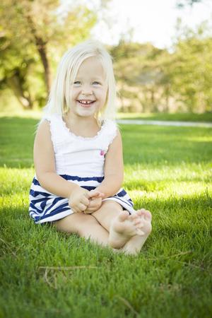 mignonne petite fille: Mignon petite fille assise et Rire dans l'herbe à l'extérieur.