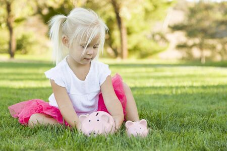 money and saving: Cute Little Girl Having Fun with Her Large and Small Piggy Banks Outside on the Grass.