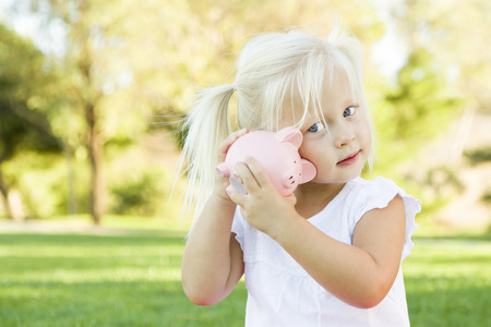 bank: Cute Little Girl Having Fun with Her Piggy Bank Outside on the Grass. Stock Photo