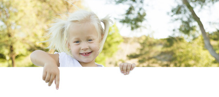text room: Cute Little Girl Outside Holding Edge of White Board with Room For Text. Stock Photo
