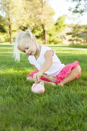 innocent: Cute Little Girl Having Fun with Her Piggy Bank Outside on the Grass. Stock Photo