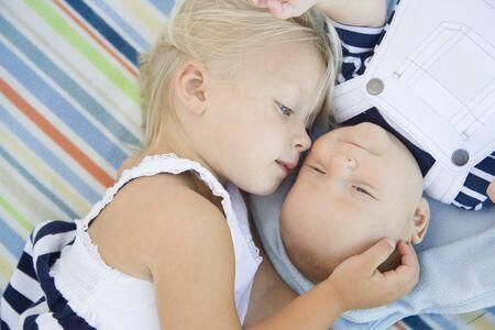 bebes recien nacidos: Cute Little Sister Acostado Junto a su hermano del bebé en la manta. Foto de archivo