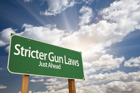 shootings: Stricter Gun Laws Green Road Sign With Dramatic Clouds and Sky.