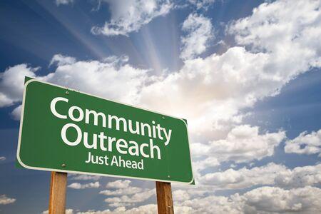 comunidad: Asistencia de la comunidad verde señal de tráfico con las nubes dramáticas y Sky. Foto de archivo