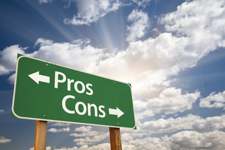 Pros and Cons Green Road Sign With Dramatic Clouds and Sky. Stock Photo