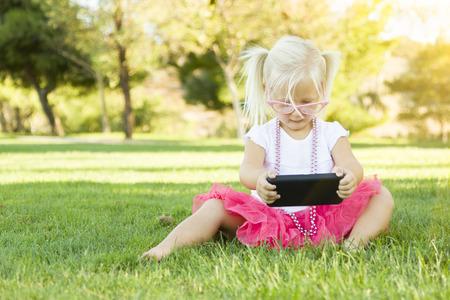 zellen: Nettes kleines Mädchen sitzen im Gras spielt mit Handy.