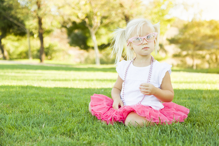 dressup: Cute Little Girl Playing Dress In The Grass Up With Pink Glasses and Beaded Necklace.