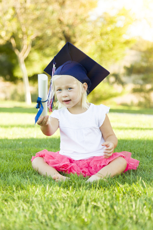young students: Cute Little Girl In Grass Wearing Graduation Cap Holding Diploma With Ribbon. Stock Photo