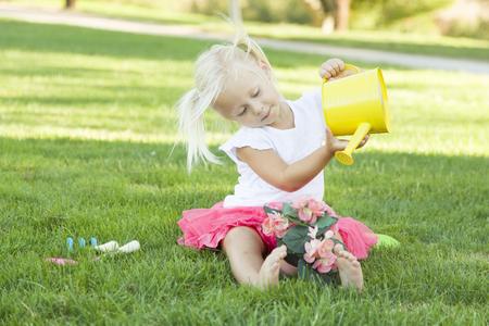 niños sentados: Niña linda que juega con su jardinero Herramientas y Tiesto.