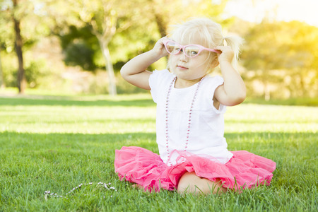 kids dress: Cute Little Girl Playing Dress In The Grass Up With Pink Glasses and Beaded Necklace.
