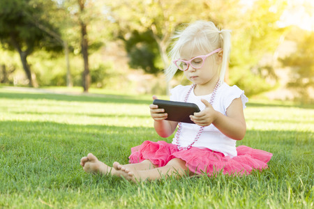 cellular: Cute Little Girl Sitting In Grass Playing With Cell Phone. Stock Photo