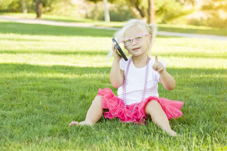 toddler: Cute Little Girl Sitting In Grass Talking on Cell Phone.
