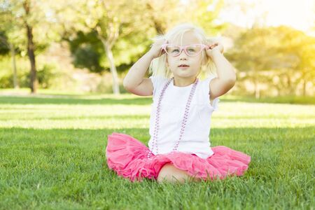 dress up: Cute Little Girl Playing Dress In The Grass Up With Pink Glasses and Beaded Necklace.