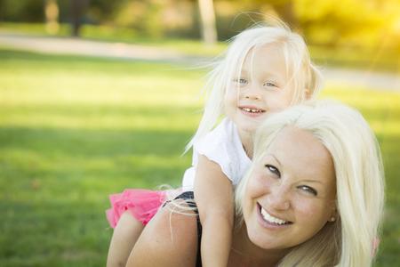 madre soltera: Madre bonita y la ni�a que se divierten junto en la hierba. Foto de archivo