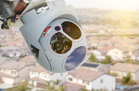 infiltration: Closeup of A Drone Wing Camera and Sensor Pod Module Above A Residential Neighborhood. Stock Photo
