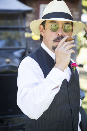 twenties: Handsome 1920s Dressed Man Near Vintage Car Smoking A Cigar. Stock Photo