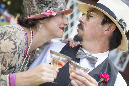 an era: Attractive Mixed-Race Couple Dressed in 1920's Era Fashion Sipping Champagne. Stock Photo