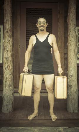 twenties: Goofy Gentleman Dressed in 1920's Era Swimsuit Holding Suitcases on Porch of Cabin.