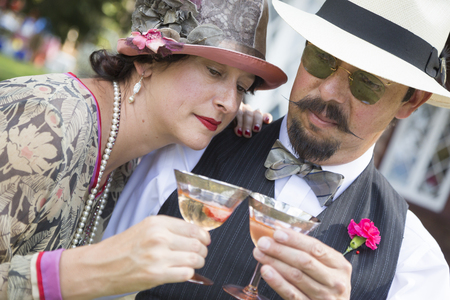 sipping: Attractive Mixed-Race Couple Dressed in 1920's Era Fashion Sipping Champagne. Stock Photo