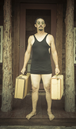 bathing costume: Goofy Gentleman Dressed in 1920's Era Swimsuit Holding Suitcases on Porch of Cabin.
