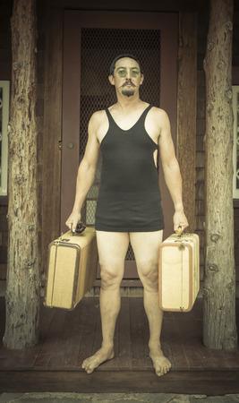 gentleman's: Goofy Gentleman Dressed in 1920's Era Swimsuit Holding Suitcases on Porch of Cabin.