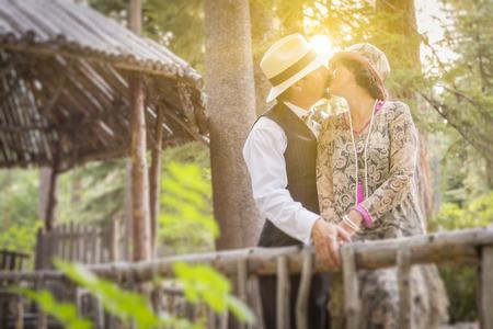 twenties: Attractive 1920s Dressed Romantic Couple Kissing on Wooden Bridge.